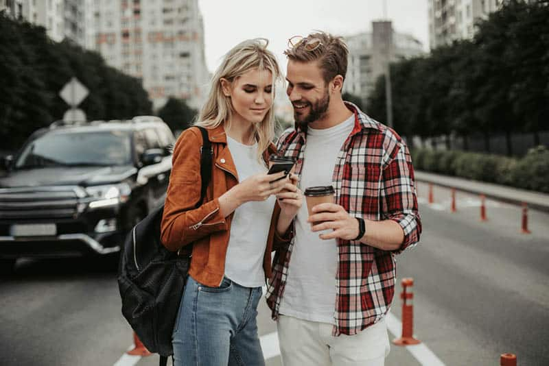 couple standing on the street watching something on phone