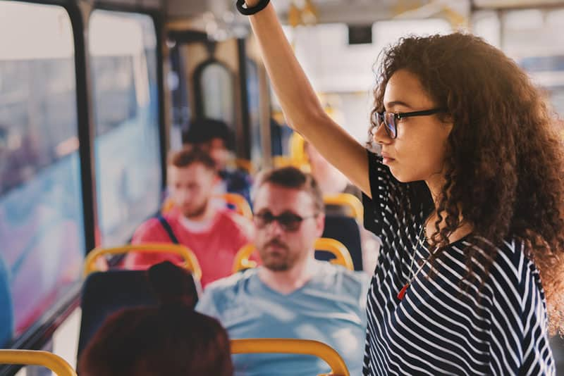 curly hair woman wearing eyeglasses while standing in public transport