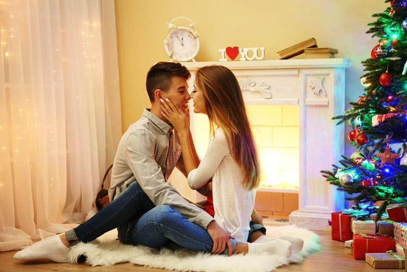 cute couple sitting next to christmas tree