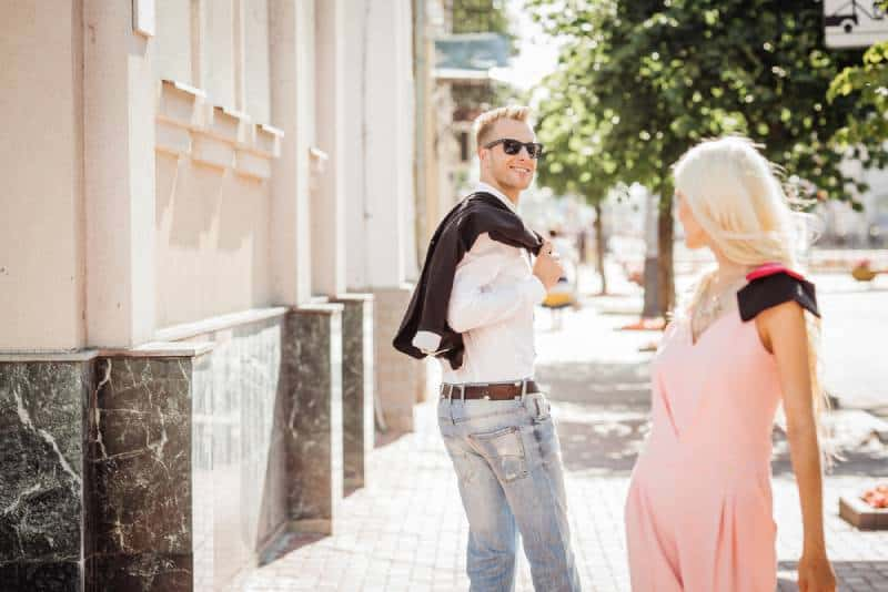 guy looking a nice girl while walking at the street