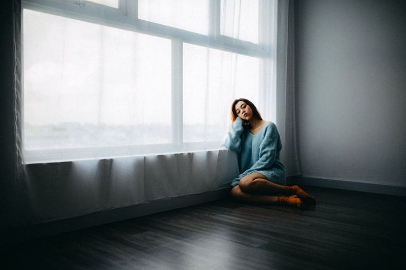 lonely woman sitting in the room on the floor