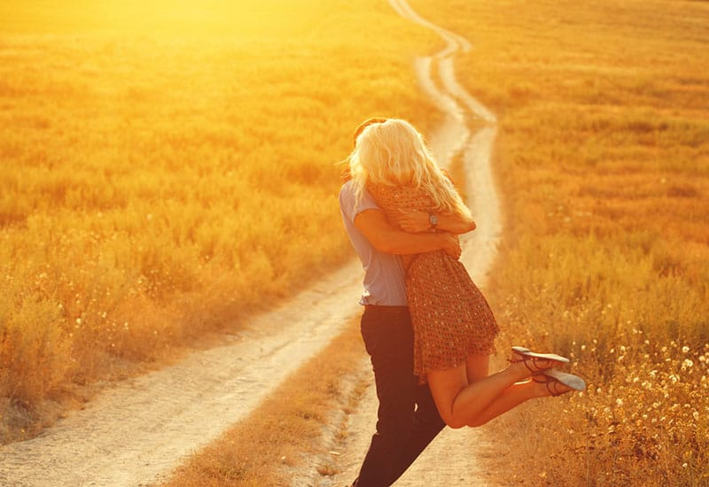 lovely couple hugging during sunset in grass field