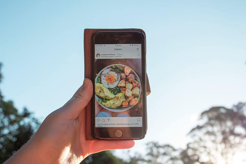 man holding phone and the picture of food on it