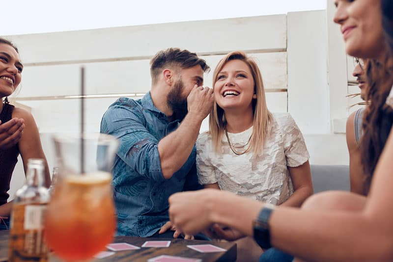 man whispering to woman around friends