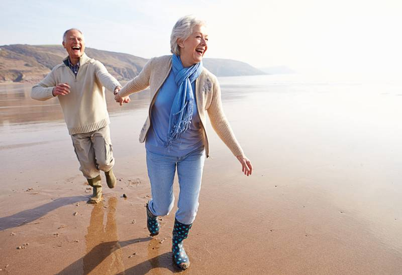 old marriage couple holding hands on the beach