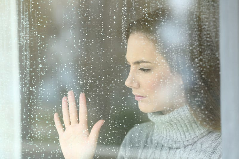 sad woman putting hand on rainy window
