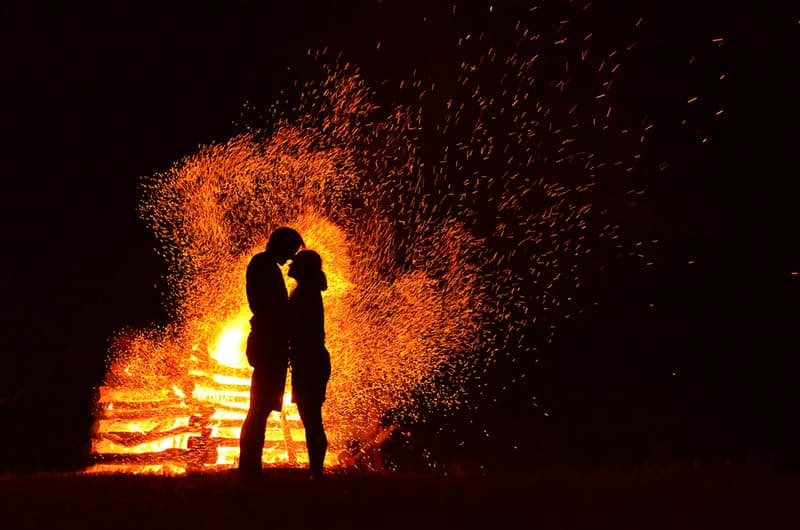 silhouette of man and woman standing beside flame