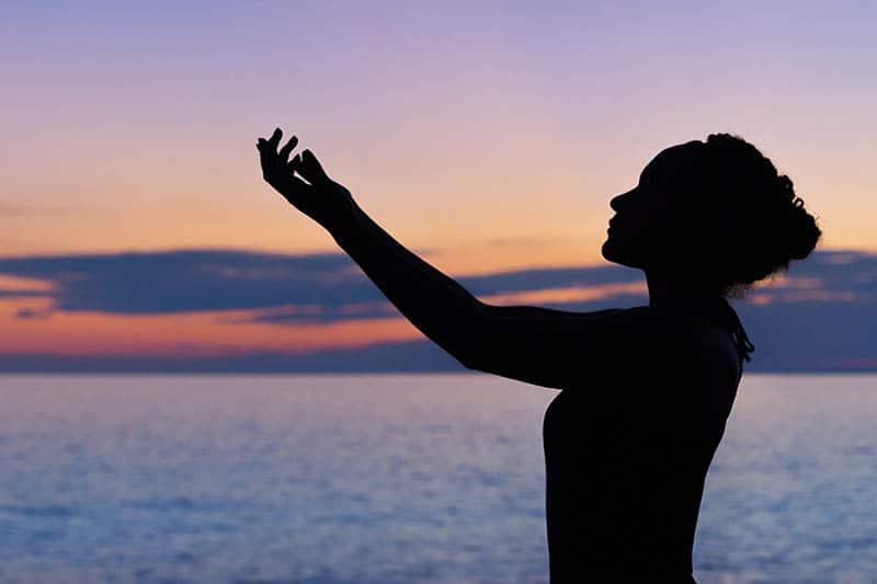 silhouette of woman raising hand beside sea