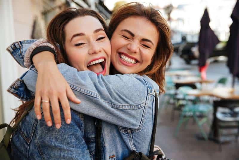 smiling friends hugging outside
