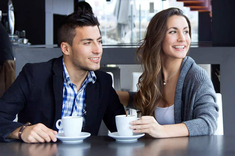 smiling man and woman at cafe looking away