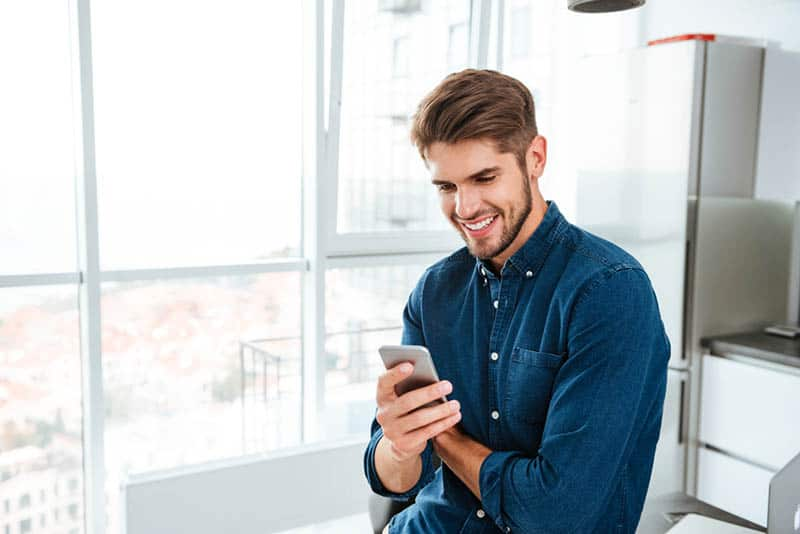 smiling man in blue shirt texting on his phone