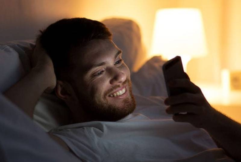 smiling man typing on his phone at night