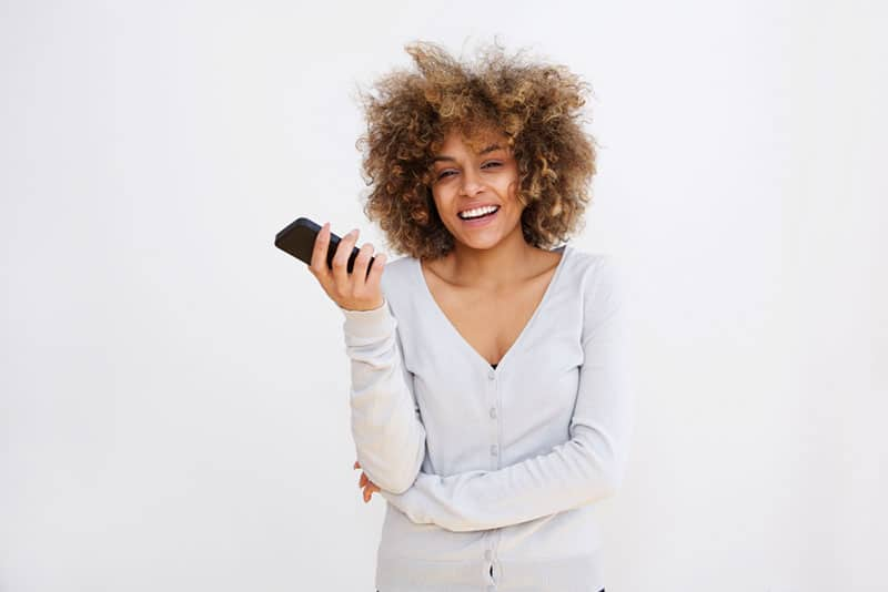 smiling woman posing with mobile phone