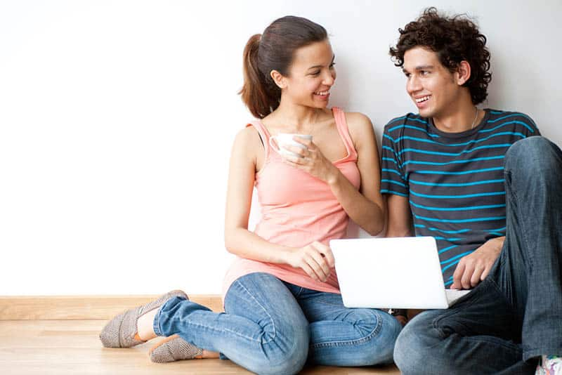 smiling young couple looking each other while sitting on floor