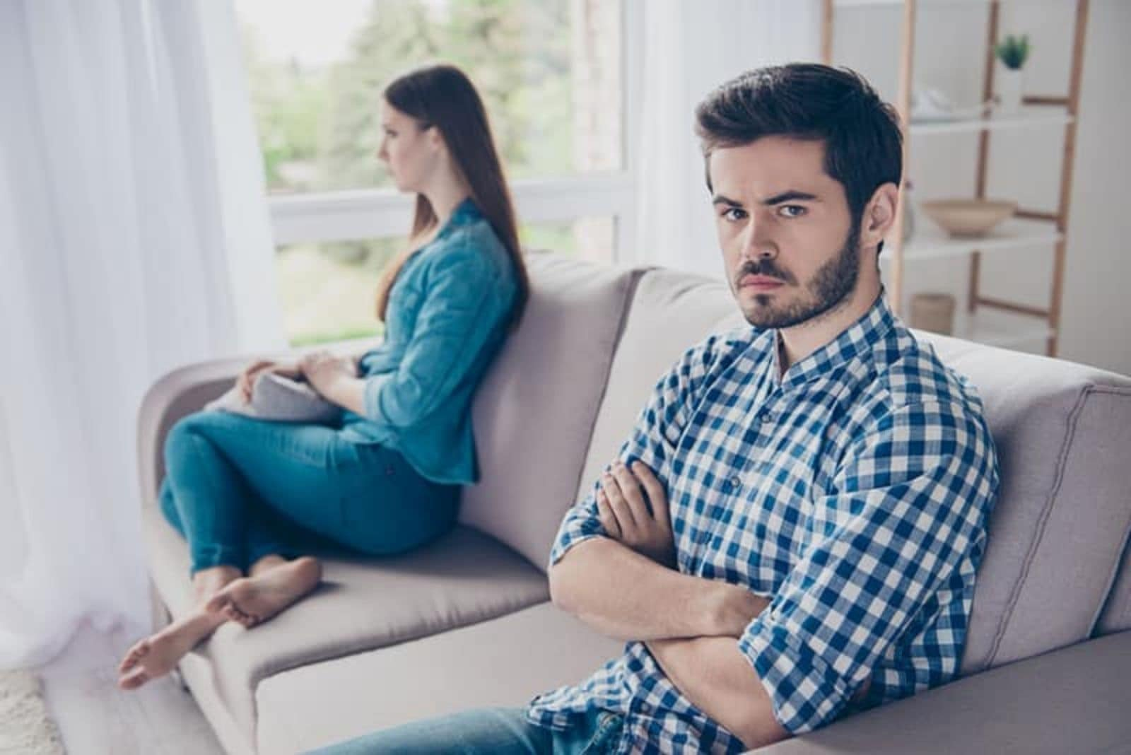 the woman turned her back on the man as they sat on the couch