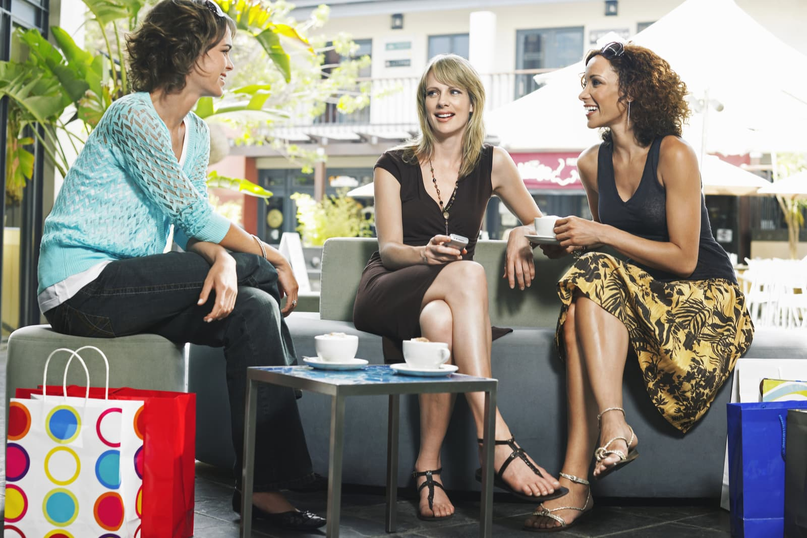 three friends sit drinking coffee and talking