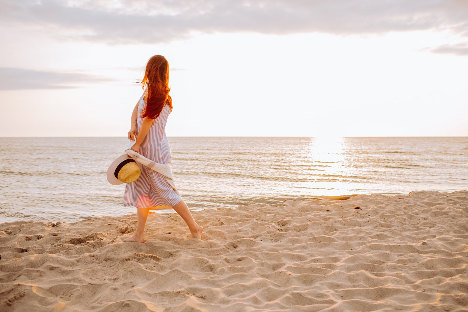 woman in a dress holding straw hat and walking alone on empty sand beach