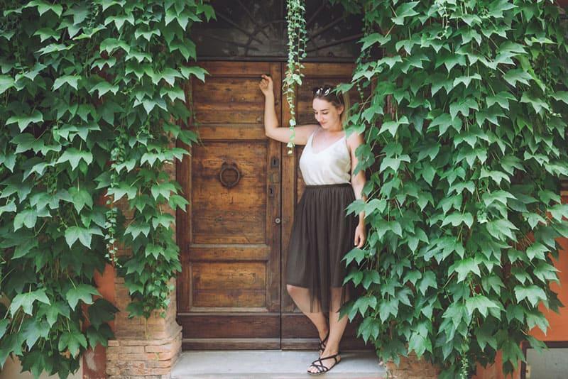 woman standing in front of wooden doors beside leafs