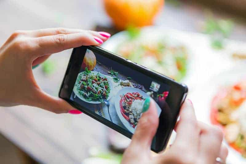 woman taking picture of food for instagram