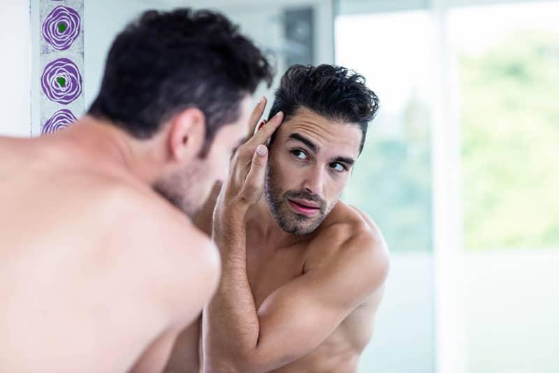 young man looking at mirror