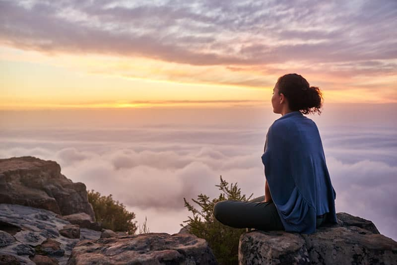 young woman sitting peacefully on mountain