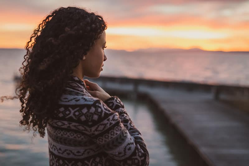 young woman with curly hair standing by the sea