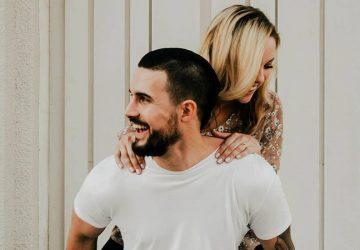 smiling man piggybacking his girlfriend