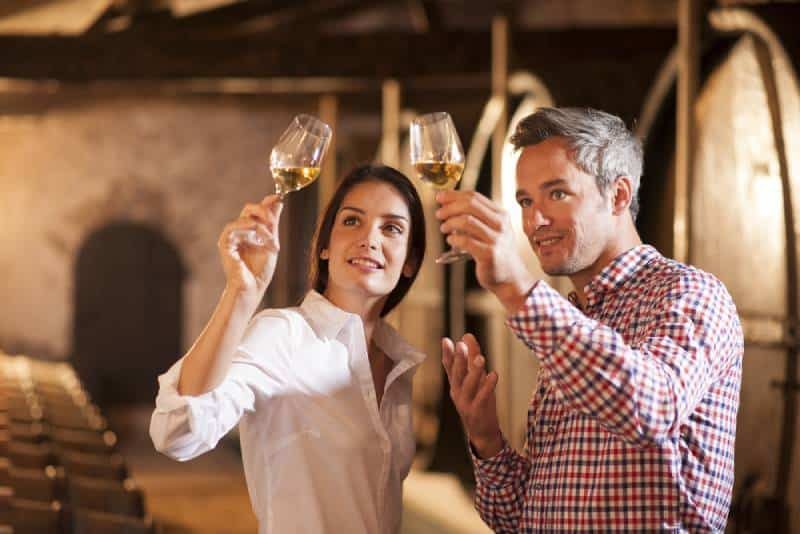 Couple enjoying a glass of white wine in a traditional cellar surrounded by wooden barrels.