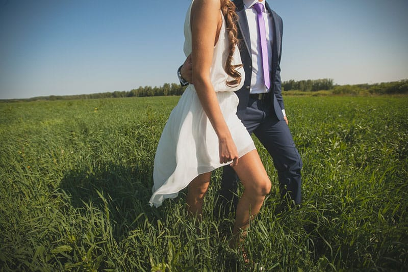 man holds woman waist while walking on grass field