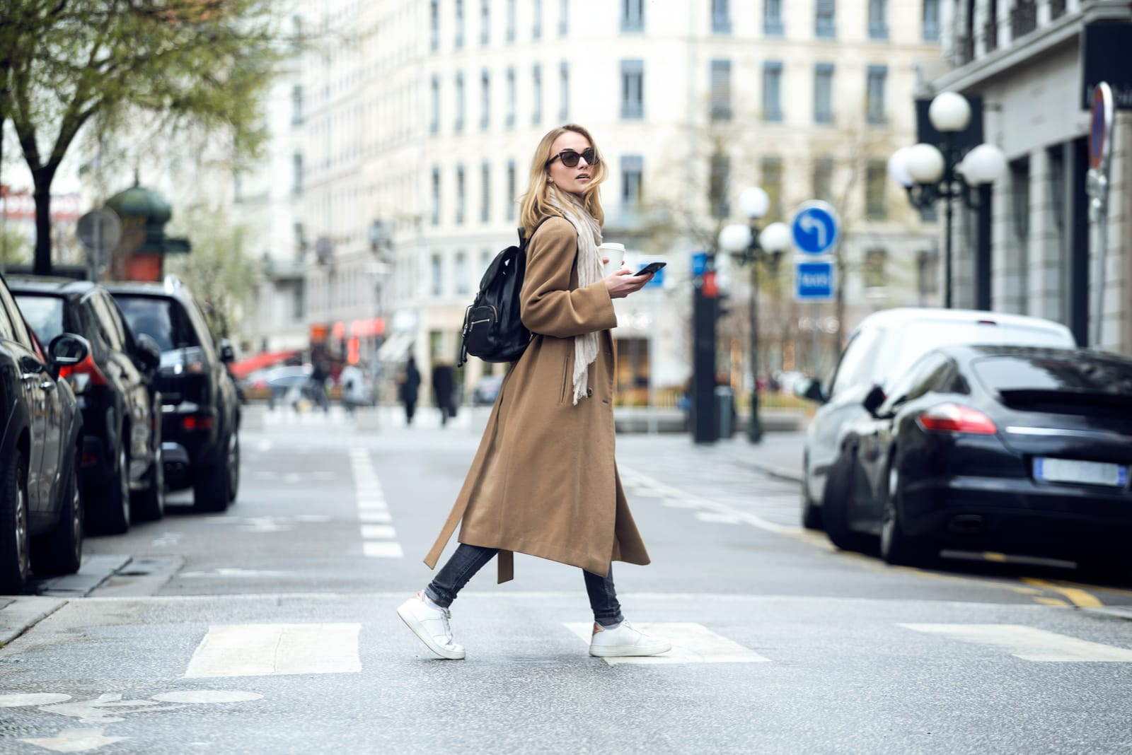 a blonde in a coat with sunglasses crosses the street