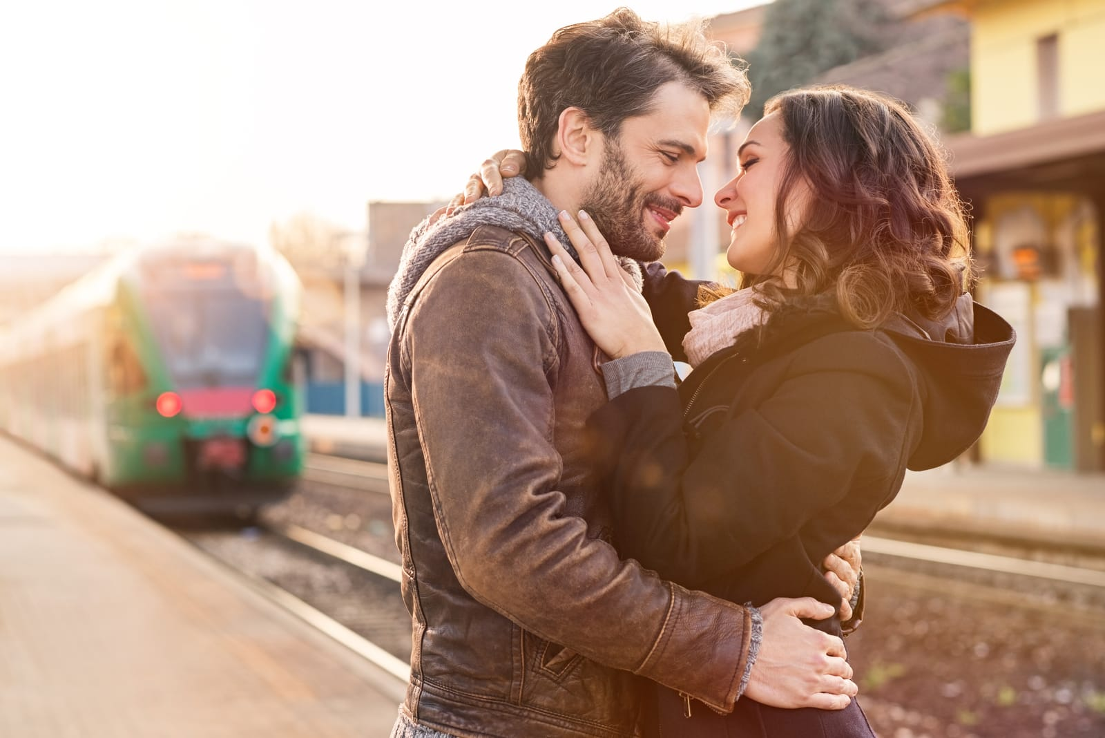 a couple in love at a train station hugging and kissing