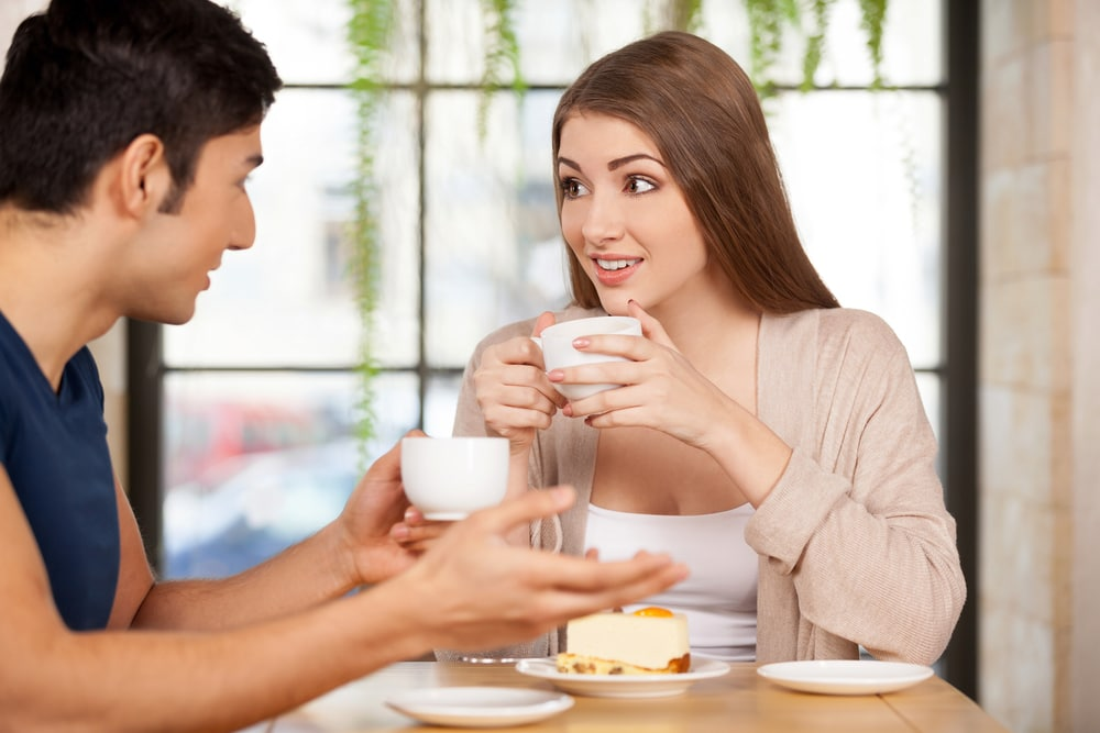 a man and a woman talking while drinking coffee