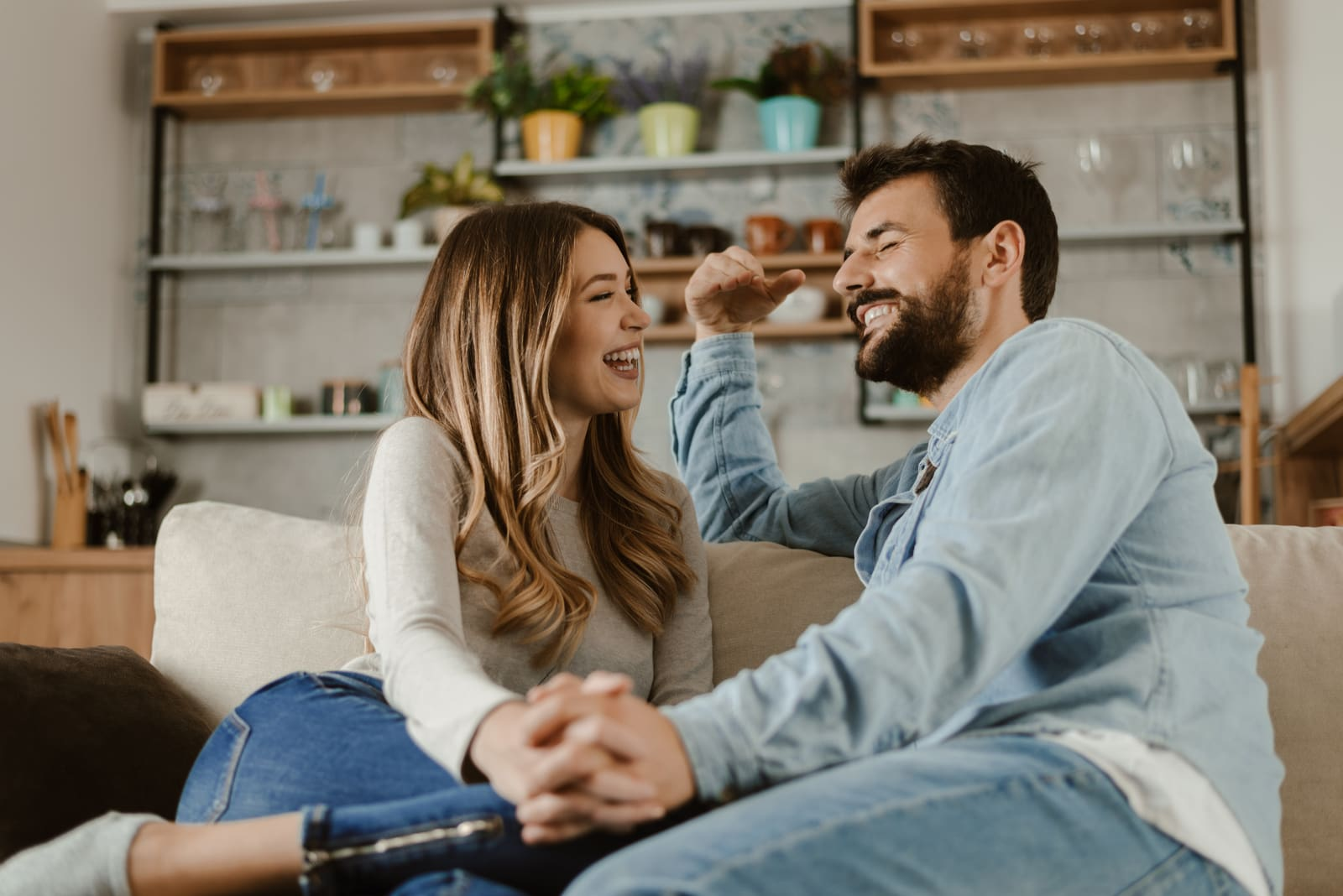 a smiling couple sits on the sofa and talks