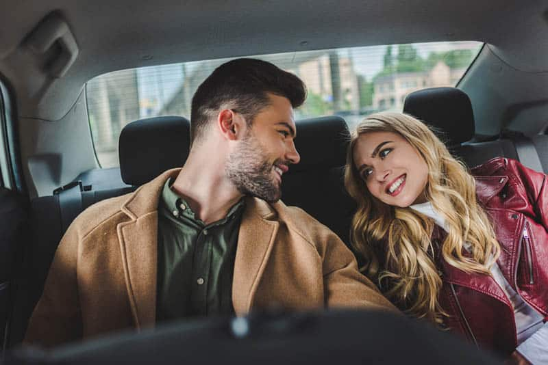 a smiling couple sitting in the back seat of a car and looking at each other