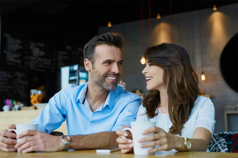 a smiling middle-aged couple sitting drinking coffee and looking at each other with a smile