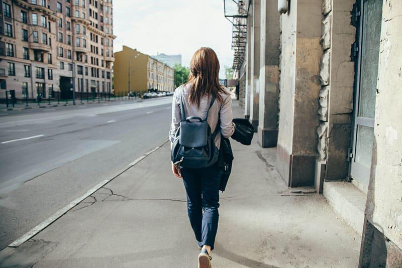back view of woman walking on sidewalk