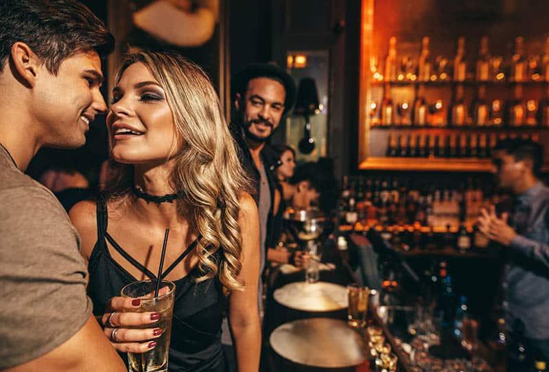 beautiful man and woman talking at bar