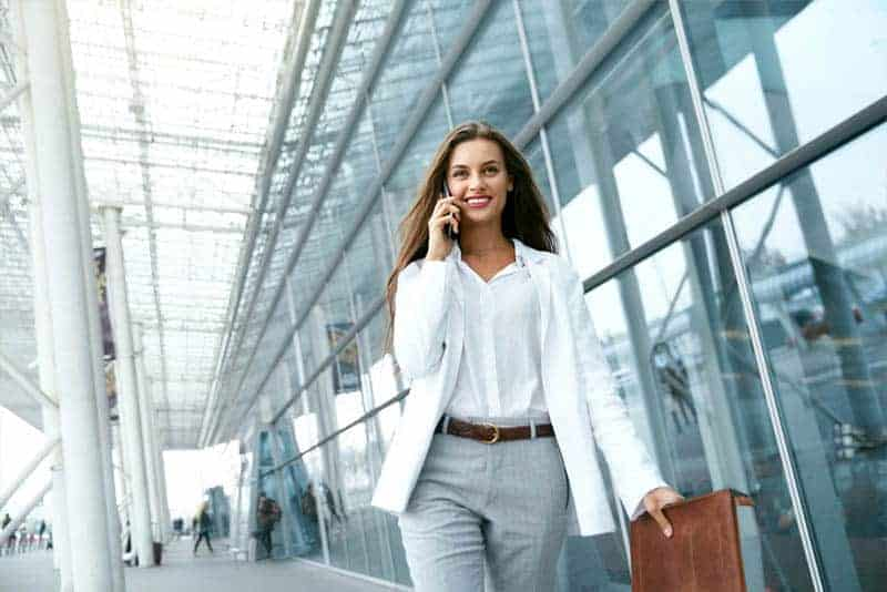business woman holding suitcase and talking on her phone