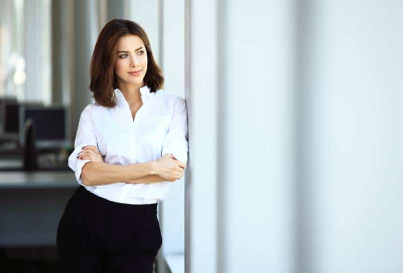 business woman in white shirt with crossed arms standing beside window