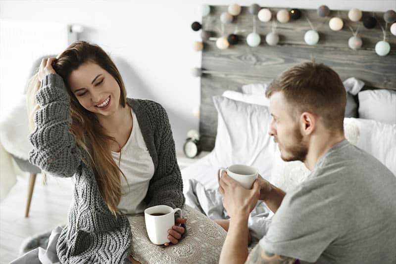 couple holding cup of tea and talking in bedroom