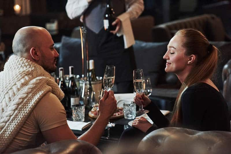couple holding glass of wine and looking at each other