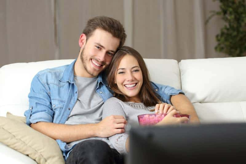 couple watching a movie on tv sitting on a couch at home