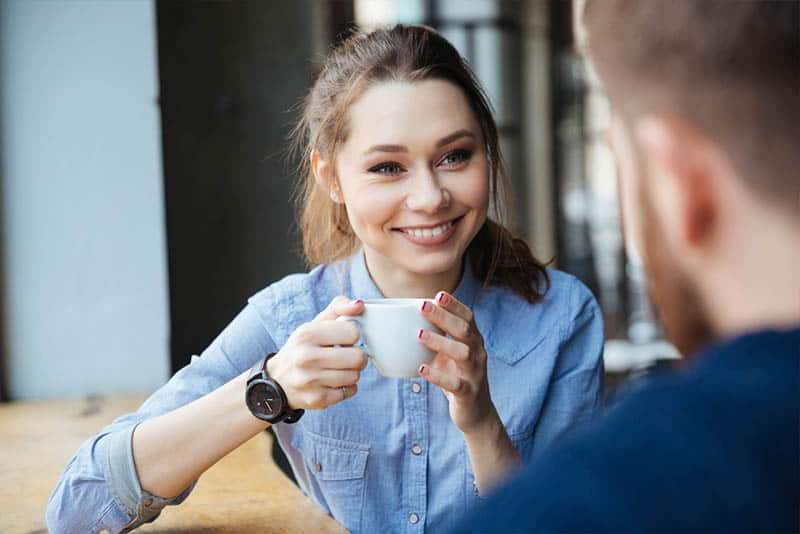 cute smiling woman holding cup of coffee and looking at man