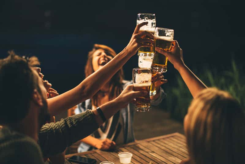 happy group of friends cheering a beers while sitting outside during night