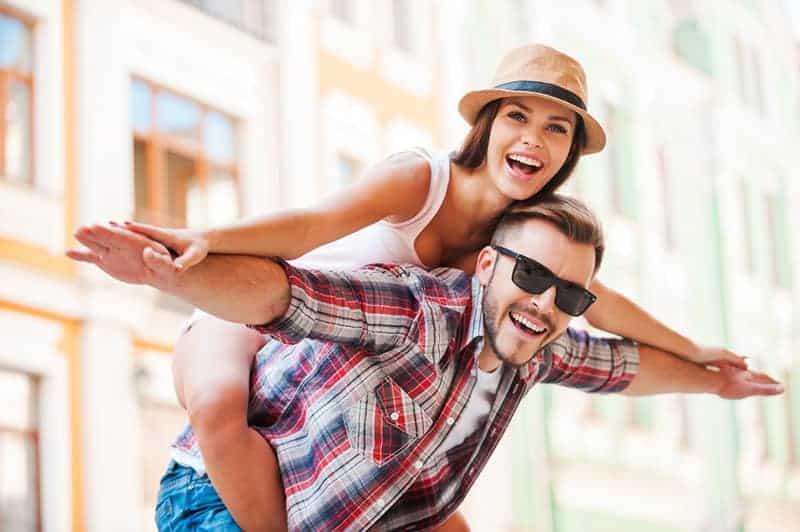 happy man piggybacking woman