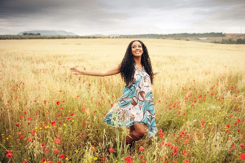 happy woman walking through the field
