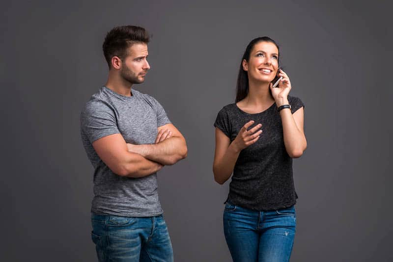 jealouse man looking at woman while she is on the phone