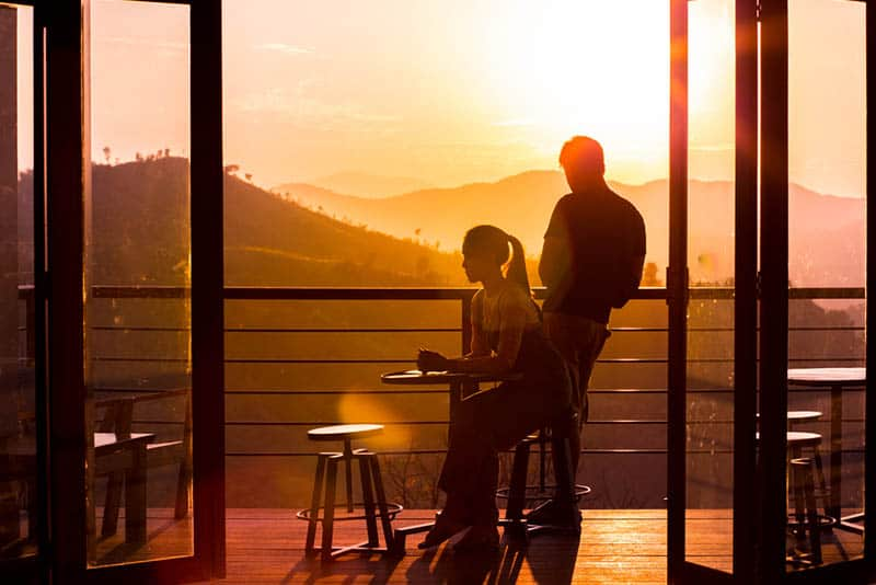 man and woman on cafe balcony during sunset