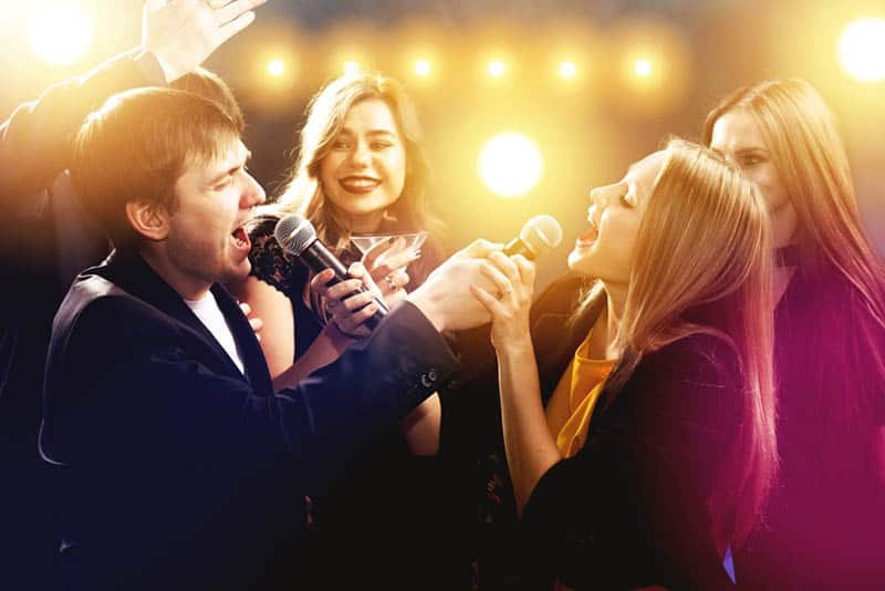 man and woman singing on microphone