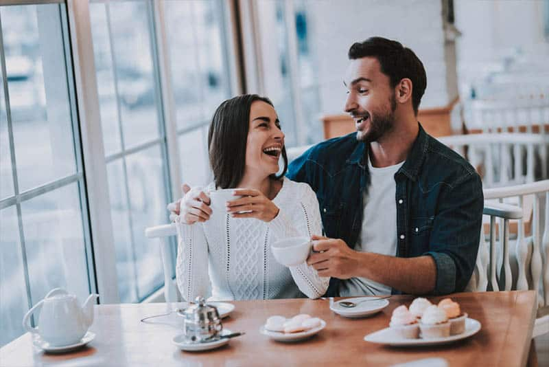 man and woman sitting at restaurant smiling and looking at each other